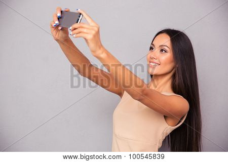 Portrait of a smiling woman in dress making selfie photo on smartphone over gray background