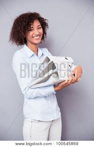 Portrait of a smiling afro american woman standing with folders on gray background and looking at camera