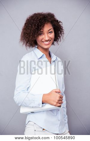 Portrait of a smiling afro american businesswoman standing with folder on gray background and looking at camera