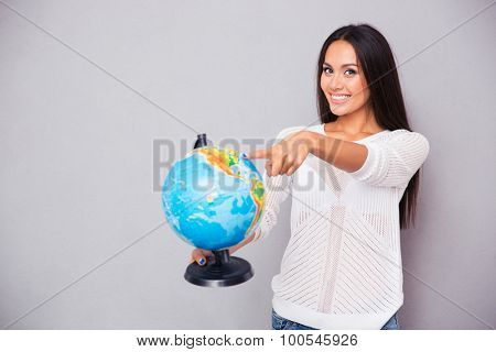 Portrait of a smiling young woman pointing finger at globe on gray background