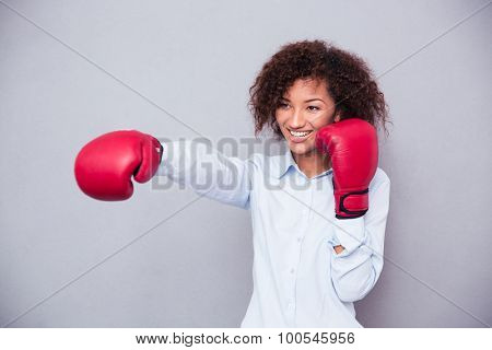 Portrait of a smiling afro american woman fighting in boxing gloves over gray abckground