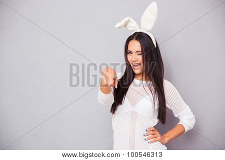 Portrait of a happy woman in bunny ears winking and pointing finger at camera over grya background