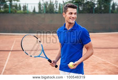Portrait of a happy man playing in tennis outdoors