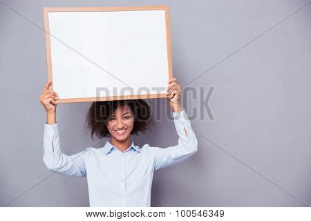 Portrait of a happy afro american woman holding blank board on gray background