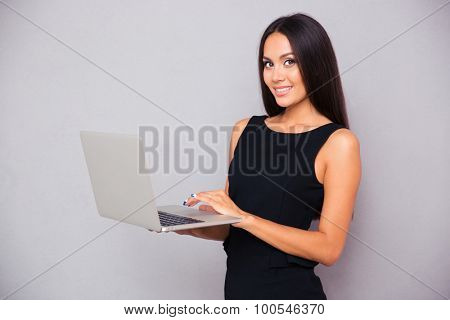 Portrait of a smiling beautiful woman using laptop on gray background and looking at camera