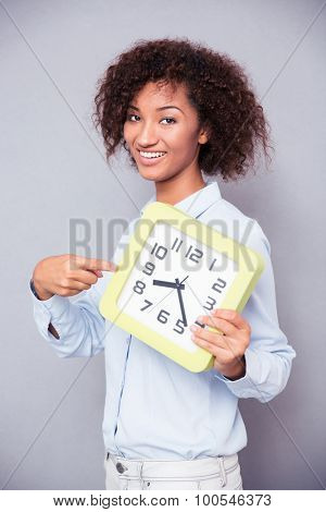 Portrait of a happy afro american woman standing with clock on gray background