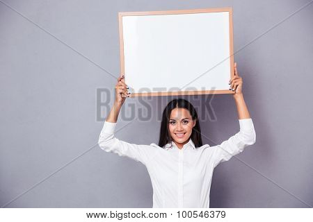 Portrait of a happy woman holding blank board on head over gray background