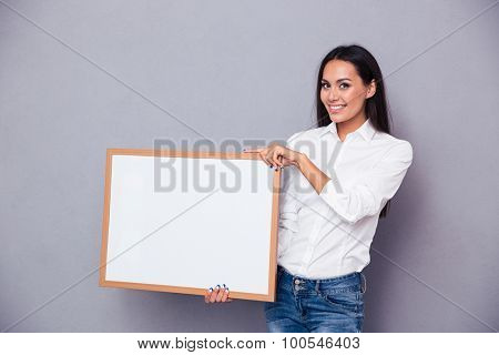 Portrait of a smiling woman holding blank board on gray background and looking at camera