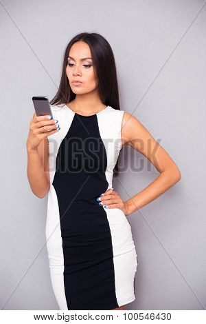 Portrait of a young woman using smartphone on gray background