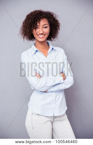 Portrait of a smiling afro american businesswoman standing with arms folded on gray background