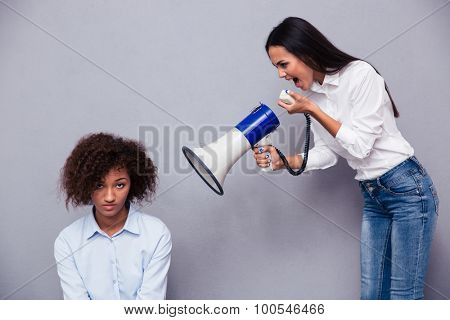 Woman shouting through loudspaker on her friend over gray background