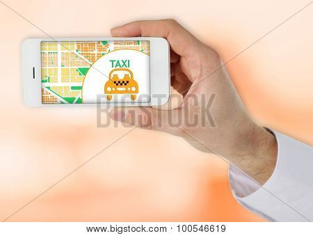 Hand holding mobile smart phone with interface taxi on light background