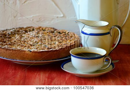 Plum crumble tart with cup of coffee creamer and coffee pot on white background.