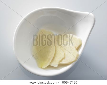 Root Ginger sliced in a bowl isolated on a white studio background.