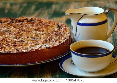 Plum crumble tart with cup of coffee and creamer on green background.