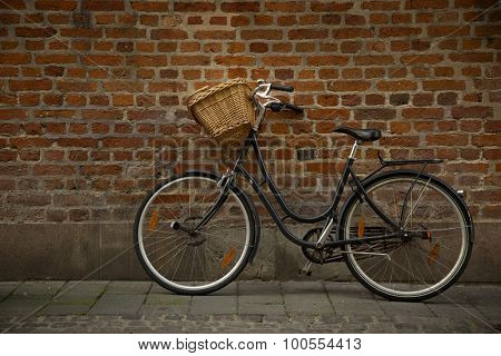 Black bicycle with straw basket along a brick wall