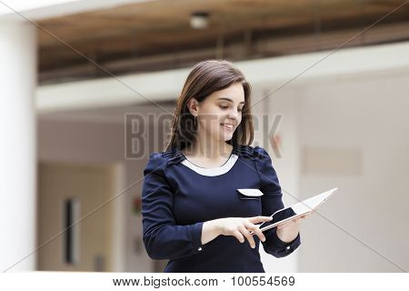 Smiling business woman with a tablet computer at office building