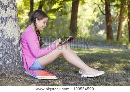Teen girl using a tablet computer outdoors