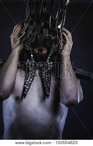 naked man with a crown of forks  in the head, concept designer kitchen