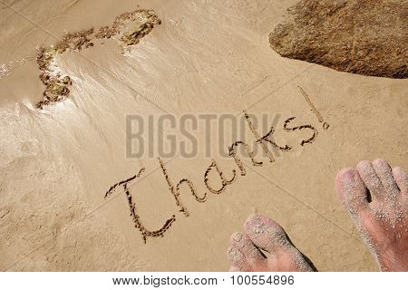 Concept or conceptual hand drawn thank you text carved in a golden sandy beach summer background with feet
