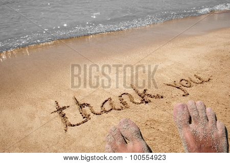Conceptual thank you handwritten text in sand on a beach in an exotic island with feet