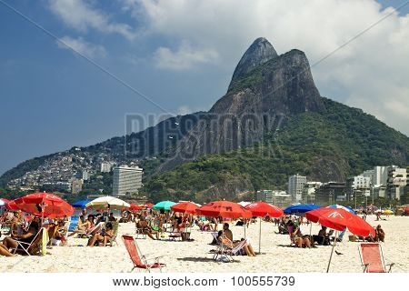 People are sunbathing relaxing under beach umbrellas on Ipanema beach in Rio de Janeiro on a hot sun