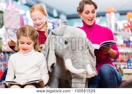 Mother with two kids shopping in toy store, one girl sitting on a plush elephant, one reading a book