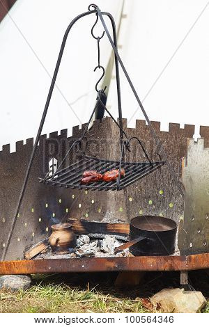 Grilled sausages on traditional campfire
