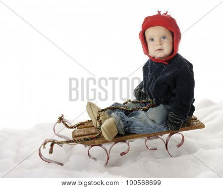 An adorable baby boy sitting on a sled in the snow, looking up questioningly.  On a white background.