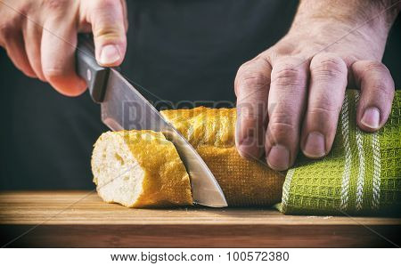 Man's hands cutting bread on the wooden plank