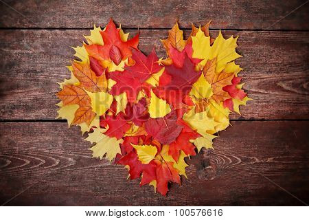 Colorful heart made of autumn leaves on a wooden background