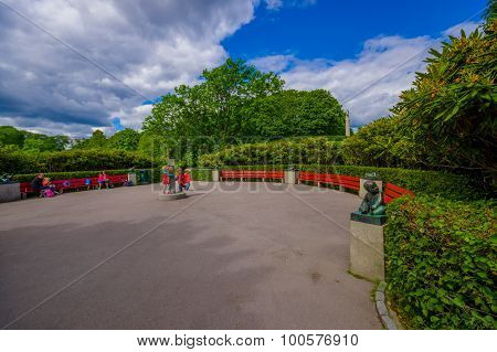 OSLO, NORWAY - 8 JULY, 2015: Gravel plaza in Vigelandsparken with red benches sorrounded by green bu