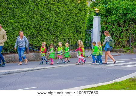 OSLO, NORWAY - 8 JULY, 2015: Group of kindergarden children walking on a line wearing reflect vests