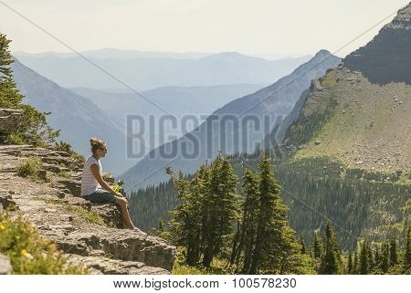 A woman sitting on a rocky ledge looking at a gorgeous view while visiting Glacier National Park in the Rocky Mountains. Large mountain range in the background with copy space