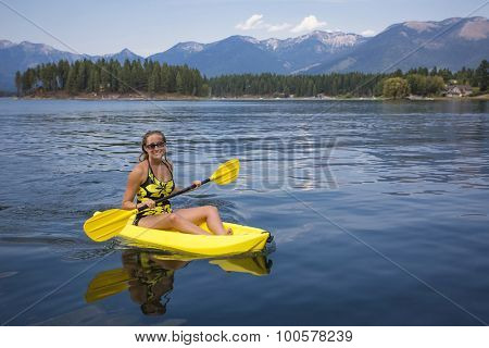 Active, Fit woman kayaking on a beautiful Mountain lake