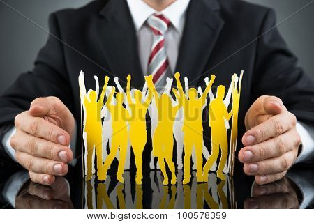 Businessperson Protecting Paper Cutout People