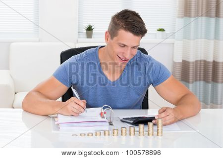 Man Calculating Invoice With Coins At Desk