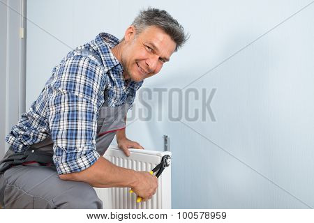 Happy Plumber Fixing Radiator