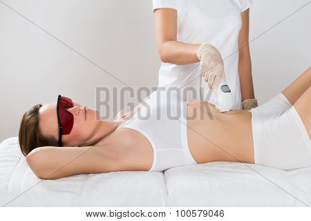 Woman Receiving Epilation Laser Treatment On Tummy