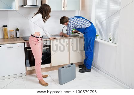 Woman Looking At Plumber Fixing Sink
