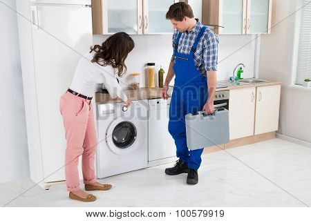 Woman Showing Damage In Washing Machine To Repairman