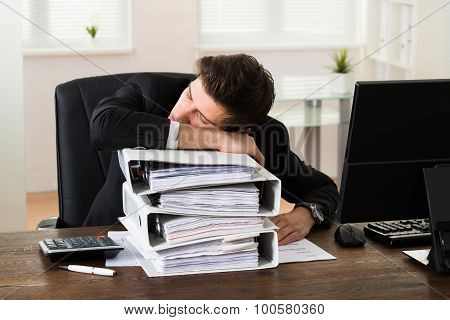 Businessman Sleeping On Binders