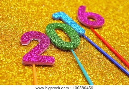 glittering numbers of different colors forming the number 2016, as the new year, on a shiny golden background