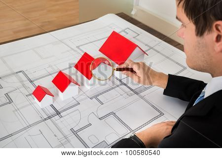 Architect Looking At House Models Through Magnifying Glass