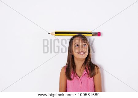 Little girl next to the wall with a giant pencil over her head