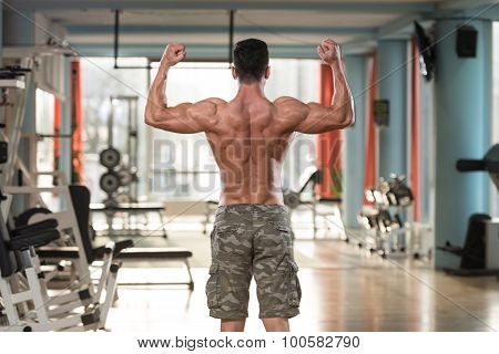 Young Man Bodybuilder Flexing Muscles