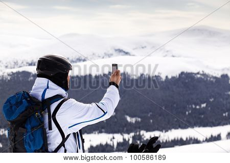 Man taking photos with phone on ski slope - winter vacation