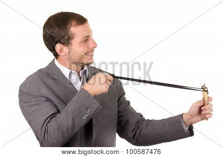 Handsome buisness man smiling concentrated aiming a slingshot isolated over white background