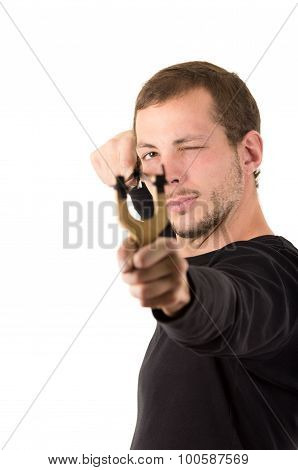Handsome man concentrated aiming a slingshot isolated over white background