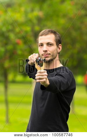Handsome man concentrated aiming  a slingshot at park having fun